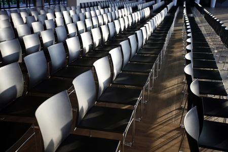Rows of empty chairs prepared for an indoor event photo