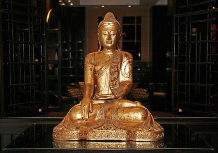 Beautiful sitting golden Buddha sculpture in a prayer hall