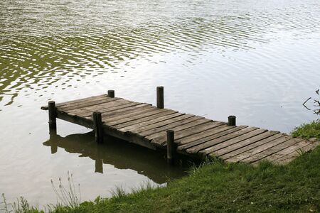 rickety: Very old wooden jetty at a peaceful fishing lake side