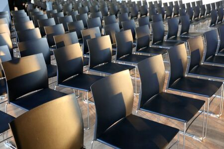 Rows of empty chairs prepared for an indoor event. Empty chairs in a modern conference room. Shallow depth of field