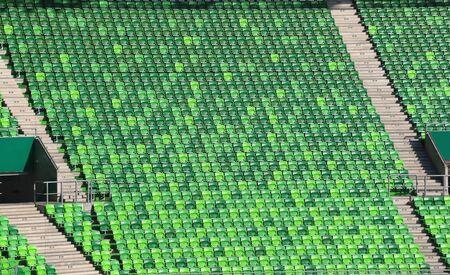 gradas estadio: Vac�as gradas verdes en el estadio de f�tbol como un fondo Foto de archivo
