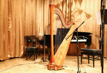 symphonic: Beautiful golden harp in the auditorium before concert Stock Photo