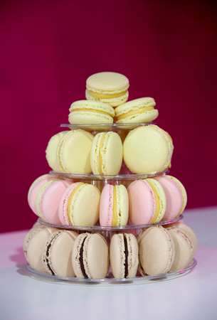 cake tier: Closeup assortment of lots of multicolored tasty macarons on tier circle cake tower display.