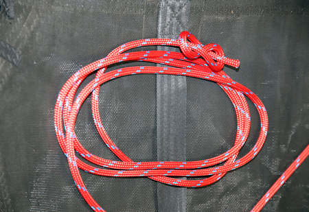 tied in: Close up figure eight knot tied in a reddish acrylic rope for sailors