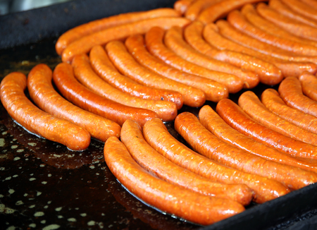 party time: Sausages baked on iron plate in row party time. Shallow depth of field Stock Photo