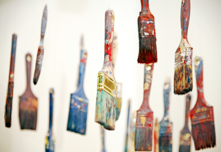 Colorful paint brushes hanging as artistic objects
