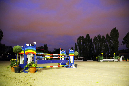 show ring: Equitation obstacles barriers at horse jumping racetrack by night