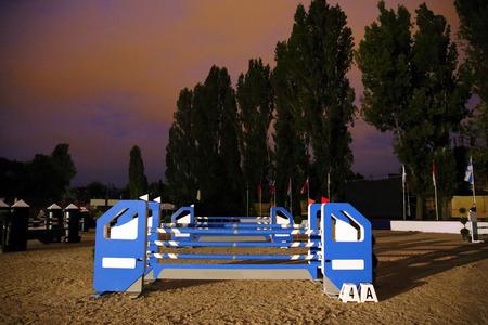 caballo saltando: obstáculos equitación barreras en caballo de salto pista de carreras por la noche Foto de archivo