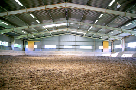 Empty riding hall with sandy covering Stock Photo