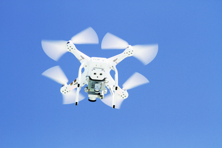 spyware: White drone  flying with camera record liens against blue sky