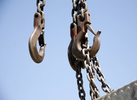 Industrial hook  with chains against a bright blue sky
