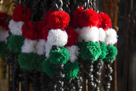 Red white and green colored whips at the farmers market for sale. Traditional tricolor leather whips for hungarian sheperds and horsemen. Shallow depth of fields