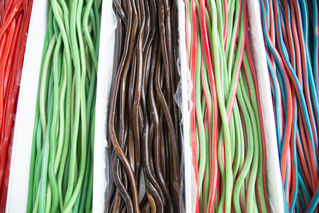 liquorice: Homemade twisted colorful twisted licorice candies as a background. Colorful tasty licorice candies for sale on retail market candy shop Stock Photo