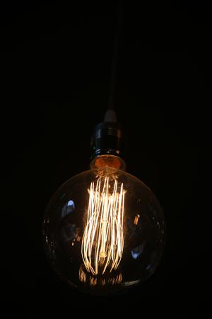Oldstyle wolfram light bulb shining in the dark Stock Photo