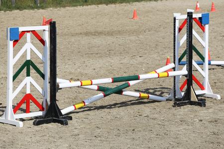 Immagine multicolore di pali di salto ostacoli all'arena di salto ostacoli. Barriere in legno per saltare i cavalli come sfondo Archivio Fotografico