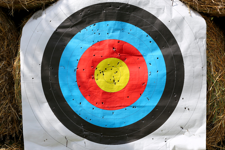 Colorful target template for sport shooting competition. Used target with color circles on shooting range against hay bales