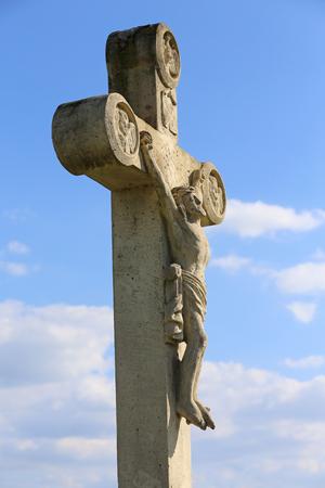 Jesus Christ on white stone cross sculpture. White stone cross against natural bue sky Stockfoto
