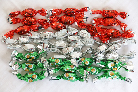 Original christmas sweetness from hungary name is szaloncukor aka parlour candy. Showing christmas sweetness fondant in colorful metal wrapping on white tablecloth Banco de Imagens