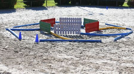 Colorful barriers on the ground for jumping horses and riders at riding school as a background.Obstacles for horses in a riding school