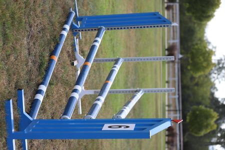 Image of show jumping poles on empty training field. Wooden barriers for jumping horses as a background. Colorful photo of equestrian obstacles. Empty field for horse jumping event competition