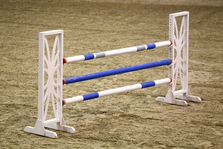 Wooden barriers for jumping horses as a background. Colorful photo of equestrian obstacles. Colorful barriers on the ground for jumping horses and riders at riding school as a background.Obstacles for horses in a riding school Stockfoto