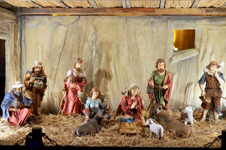 New born Jesus lying in crib or manger in the barn. Figurines of virgin Mary and saint Joseph in the stable. Nativity scene of Holy family. Christmas celebration