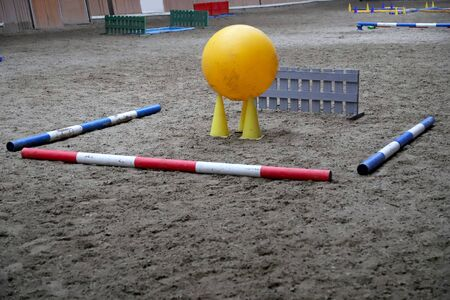 Colorful obstacles waiting for horse riders at rural equestrian centre
