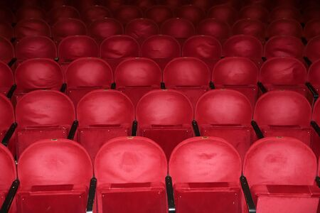 Classic rows of empty reddish seats in theatre. Hall without visitors. Shallow depth of field