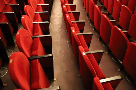 Classic rows of empty reddish seats in theatre. Hall without visitors. Shallow depth of field 版權商用圖片