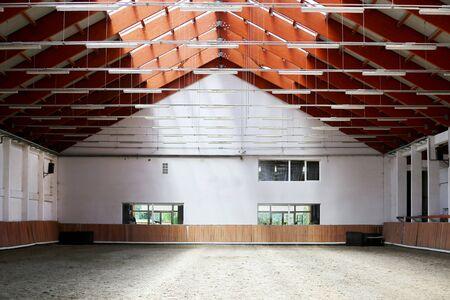 Ver en una sala de equitación interior vacía para caballos y jinetes. La escuela de equitación es apta para caballos de doma y salto.