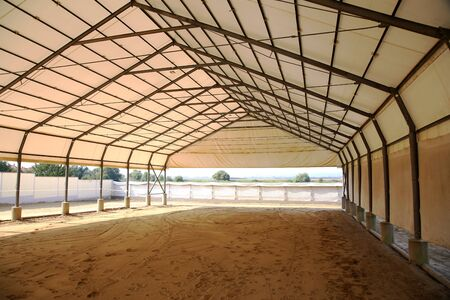 View in an empty indoor riding hall for horses and riders. The riding school is suitable for dressage and jumping horses Foto de archivo