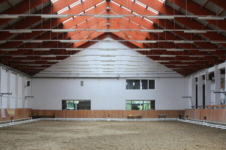 View in an empty indoor riding hall for horses and riders. The riding school is suitable for dressage and jumping horses