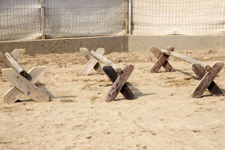 Image of poles on empty training field. Wooden barriers for horses as a background. Colorful photo of equestrian obstacles. Empty field for equestrian training