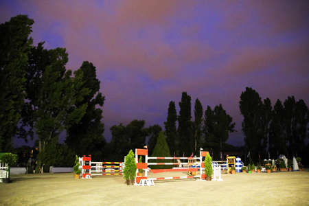 Equitation obstacles barriers at horse jumping racetrack by night