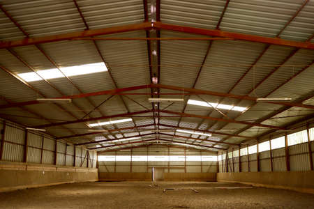 View in an empty indoor riding center for horses and riders. The riding school is suitable for training horses Standard-Bild