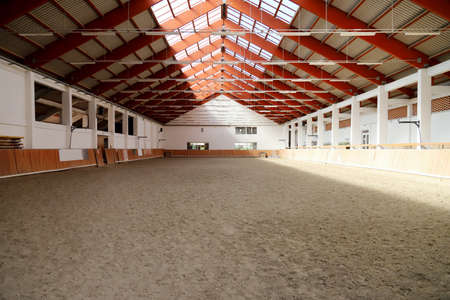 View in an empty indoor riding center for horses and riders. The riding school is suitable for training horses