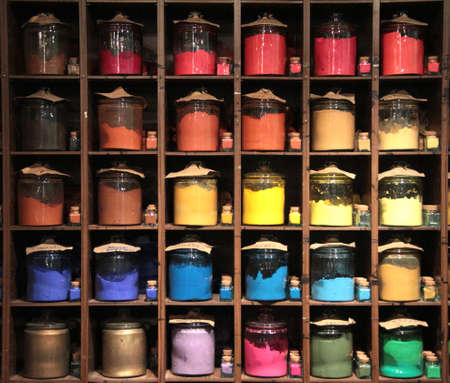 Colorful dye in glass containers in a row on shelves in a paint shop for sale