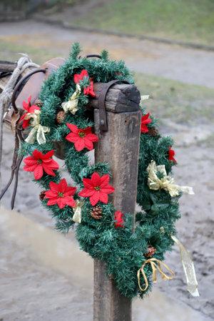 Beautiful handmade christmas garland wreath decoration hanging on wooden horse dock at rural animal farm 免版税图像