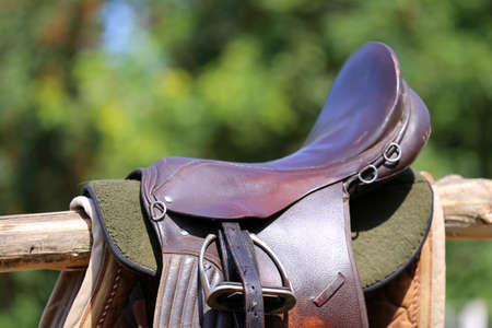 Old leather saddle with stirrups for show jumping race Saddle on a back of a sport horse. Equestrian sport event background 免版税图像