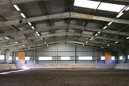 Photo of an empty indoor riding hall for horses and riders. The riding school is suitable for dressage and jumping horses all day