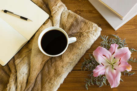 office desk: Wooden desk with a cup of coffee, notebook and flower. Soft fur on the table creates a girly, romantic and cozy atmosphere.