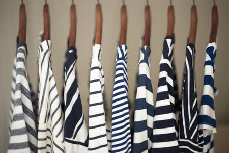 fashion clothing: A row of navy striped tops for women on wooden hangers in a closet
