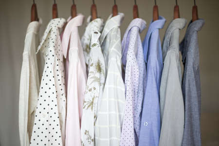 hangers: A row of assorted business shirts for women on hangers in a closet