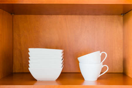 simple store: Decluttered minimalistic kitchen cabinet for simple living. Contains only essentials: white porcelain bowls and coffee or tea cups.