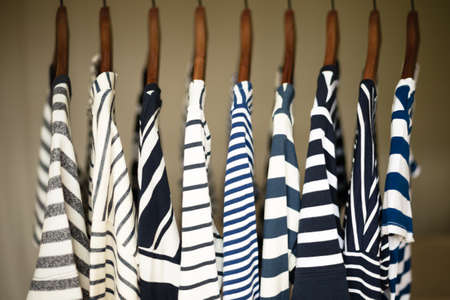 blue stripe: A row of navy striped tops for women on wooden hangers in a closet