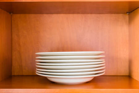 food store: Decluttered minimalistic kitchen cabinet for simple living. Contains one single type of plates: white porcelain pasta or soup bowl plates.