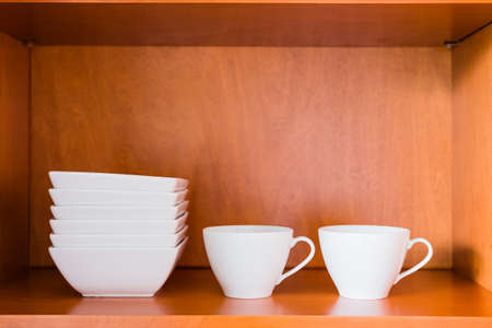 kitchen cabinets: Decluttered minimalistic kitchen cabinet for simple living. Contains only essentials: white porcelain bowls and coffee or tea cups.
