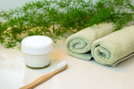 Zelfgemaakte tandpasta in stenen pot en bamboe biologisch afbreekbaar, composteerbaar tandenborstel. Gerold groen handdoeken in een spa-instelling. Groene plant decor op de achtergrond. Badkamer Wit aanrecht. Stockfoto