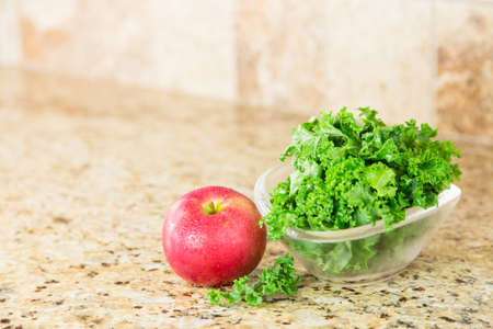 granite countertop: Red apple and a bowl of fresh green kale in a glass bowl on a granite countertop. Copy space. Stock Photo