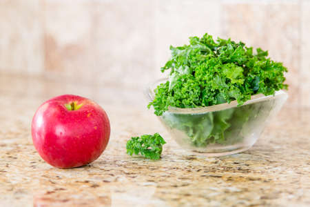 granite countertop: Red apple and a bowl of fresh green kale in a glass bowl on a granite countertop.
